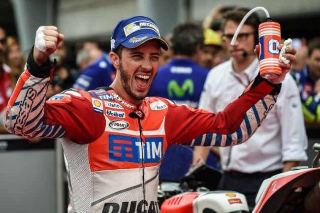Ducati Team's Italian rider Andrea Dovizioso celebrates at the parc ferme after getting pole position after the qualifying session of Malaysian MotoGP at the Sepang International circuit on October 29, 2016. / AFP PHOTO / MOHD RASFAN