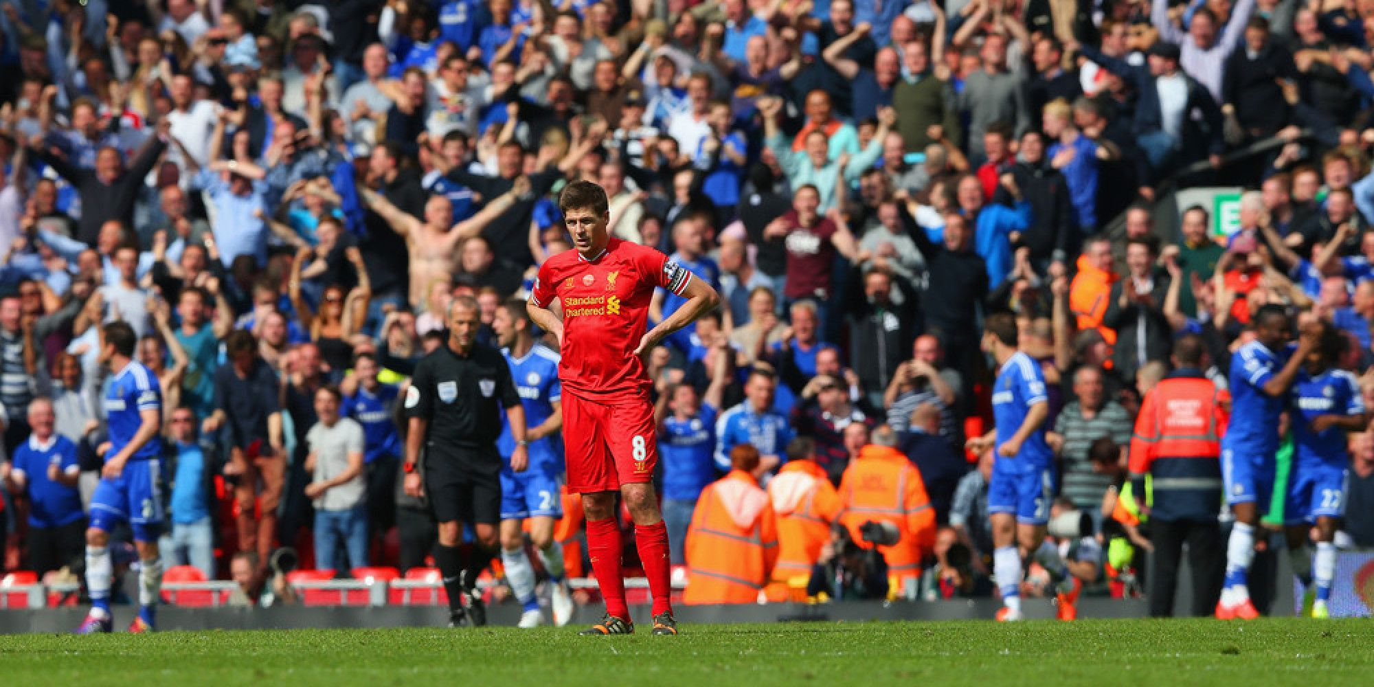 LIVERPOOL, ENGLAND - APRIL 27:  A dejected Steven Gerrard of Liverpool looks on as the Chelsea fans celebrate after Willian of Chelsea scored their second goal during the Barclays Premier League match between Liverpool and Chelsea at Anfield on April 27, 2014 in Liverpool, England.  (Photo by Clive Brunskill/Getty Images)