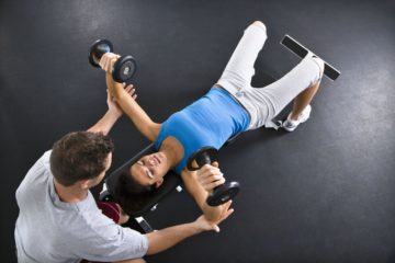02A13P3Z; Man assisting woman lifting weights at gym.